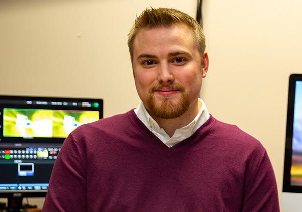 Nick Venuti smiles as he sits at a video editing desk.
