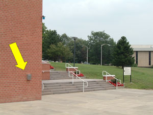 arrow pointing to blue light phone on the Decker Centeron the Southeast corner (at base of stairs near Student Lot #1)